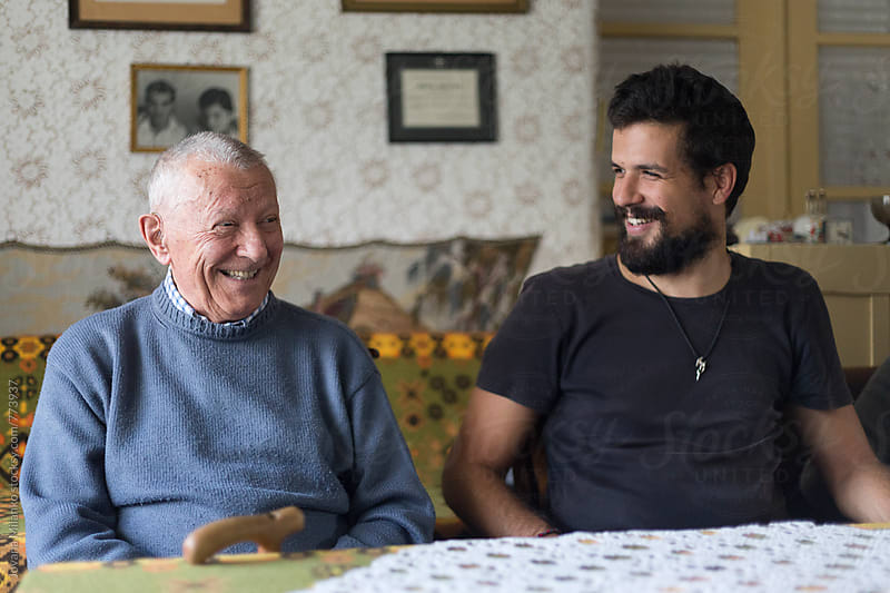 Grandfather and his adult grandson chatting at the table in the livingroom by Jovana Milanko for Stocksy United