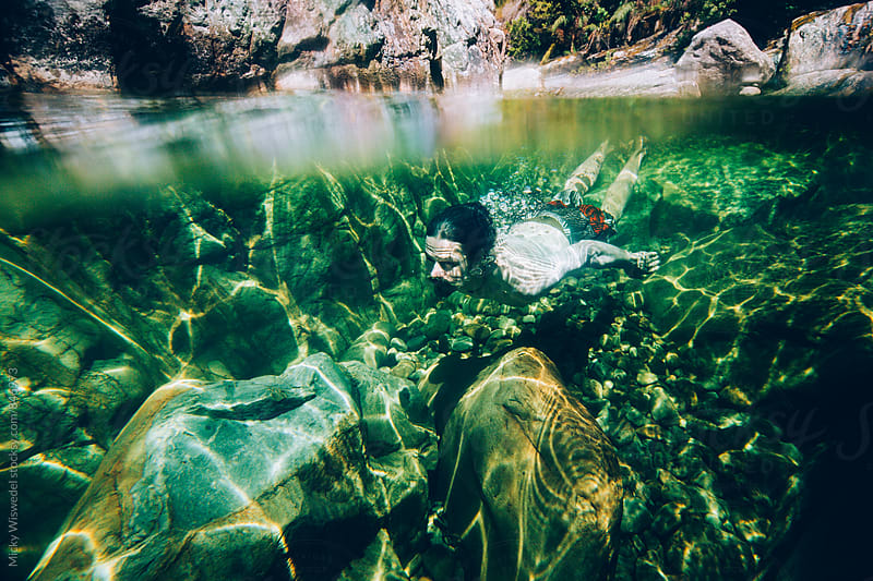 man swimming underwater in a mountain river rock pool by Micky Wiswedel for Stocksy United