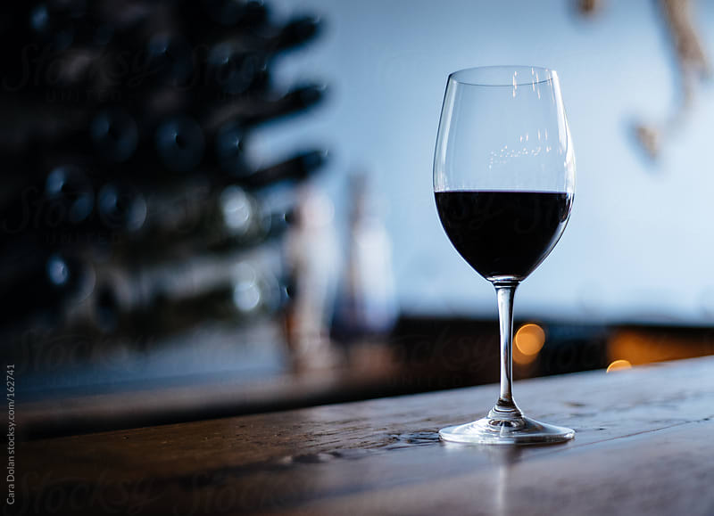 Single glass of wine on the bar top at a wine bistro by Cara Dolan for Stocksy United