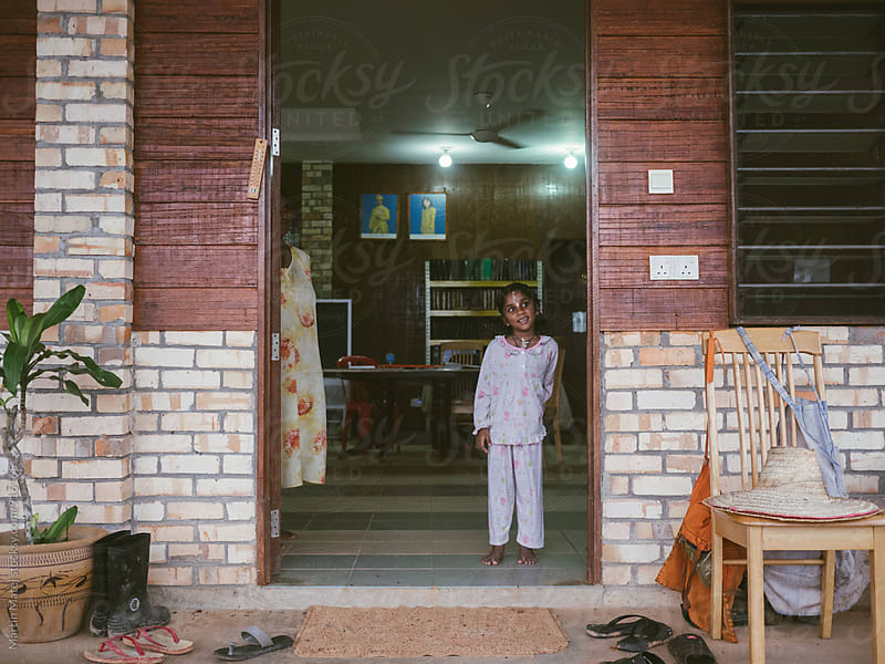 Young indian child standing in door to home by Martin Matej for Stocksy United