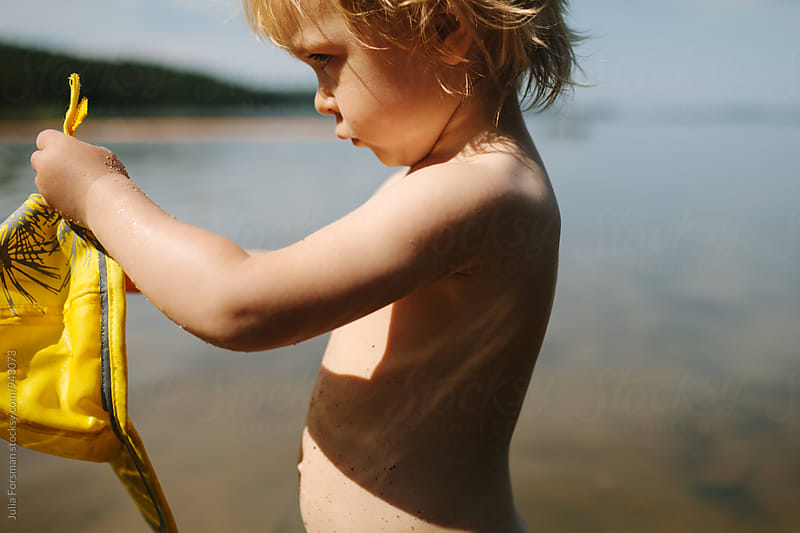 Little girl looks at the yellow hat she is holding while standing in the water of the Finnish Archipelago. by Julia Forsman for Stocksy United