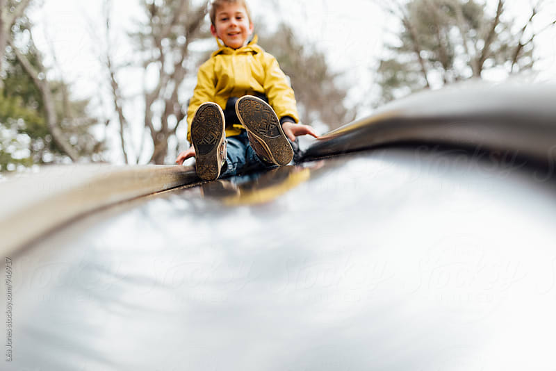 child ready to go down a slide by Léa Jones for Stocksy United