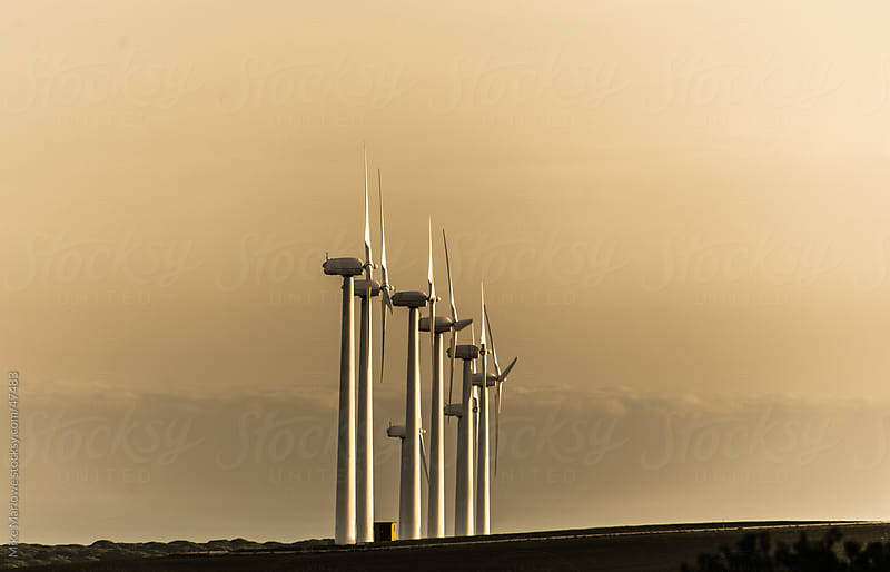 Side view of wind turbines at sunset. by Mike Marlowe for Stocksy United
