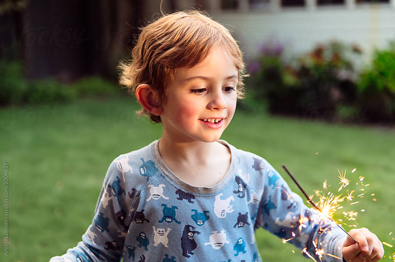 Happy boy enthralled by  the light of a sparkler in the garden in the evening by Angela Lumsden for Stocksy United