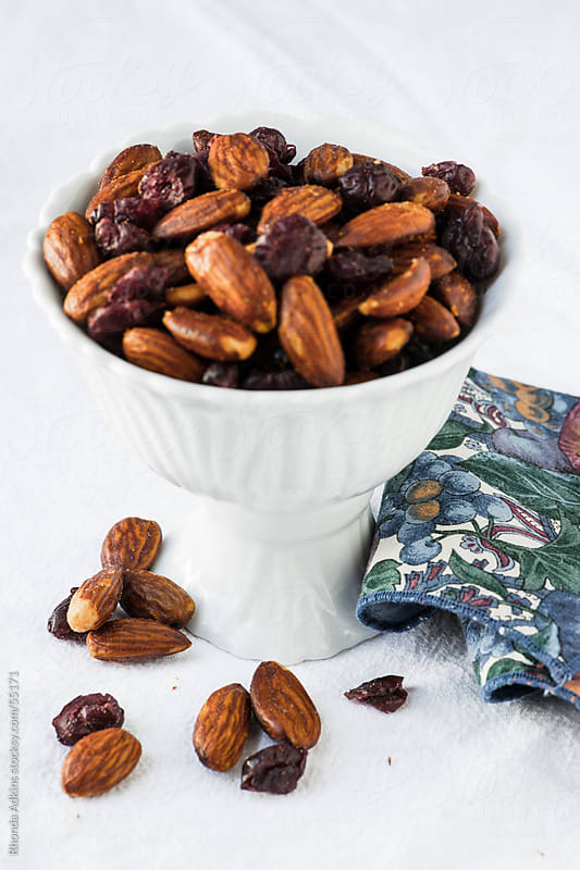 Salted Almonds and Dried Cranberries in a white footed serving bowl by Rhonda Adkins for Stocksy United
