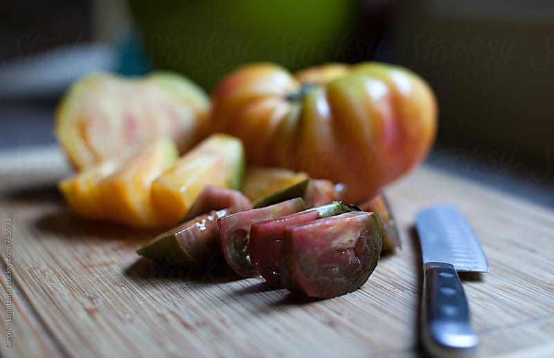 Colorful, organic heirloom tomatoes on the cutting board by Carolyn Lagattuta for Stocksy United