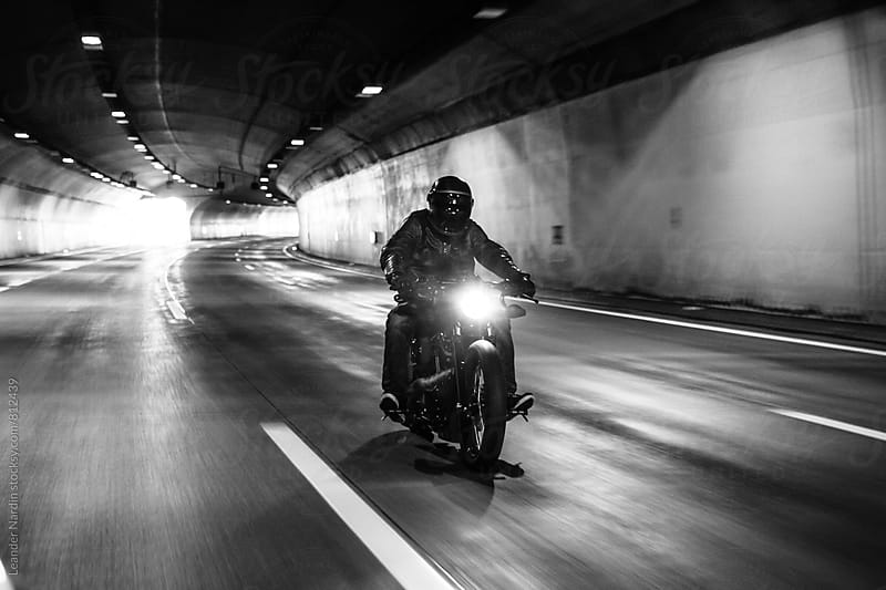 dark rider riding his bike in a tunnel - black and white by Leander Nardin for Stocksy United