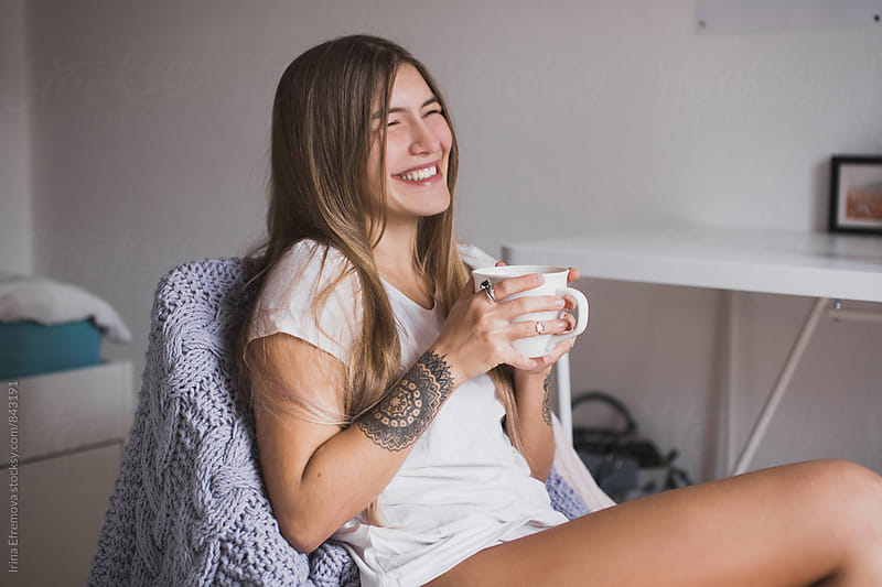 Smiling girl drinking tea by Irina Efremova for Stocksy United