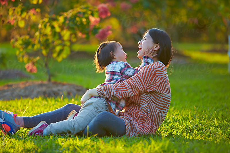 little asian girl with her mother in the park by Bo Bo for Stocksy United