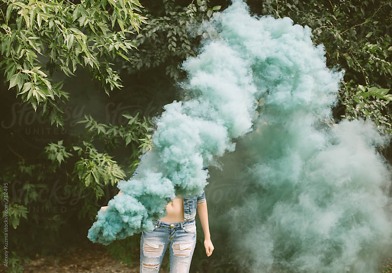 young woman with green smoke bomb at nature by Alexey Kuzma for Stocksy United