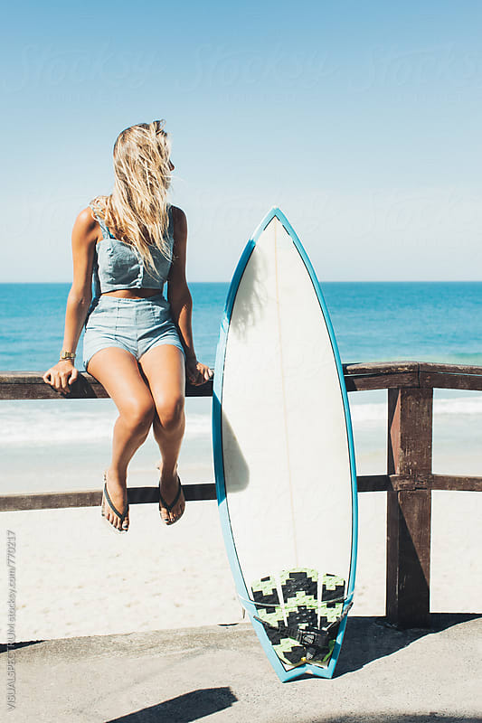 Blond Female Surfer Girl Sitting Next to Surfboard on Ipanema Beach in Rio de Janeiro by VISUALSPECTRUM for Stocksy United