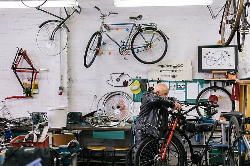 Senior Bicycle Mechanic working in workshop  by VegterFoto for Stocksy United