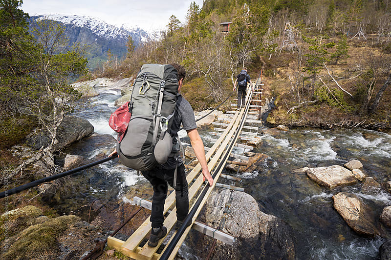 two males crossing a river on a suspension bridge while hiking in Norway. by Tristan Kwant for Stocksy United