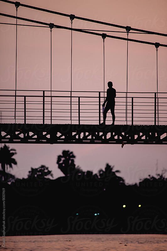 Man walking across the bridge by Chalit Saphaphak for Stocksy United