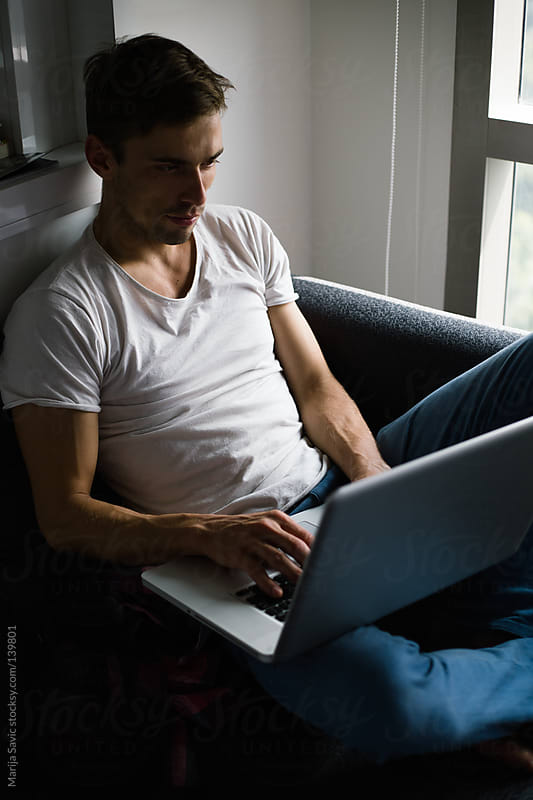 Young Man Working on Laptop at Home by Marija Savic for Stocksy United