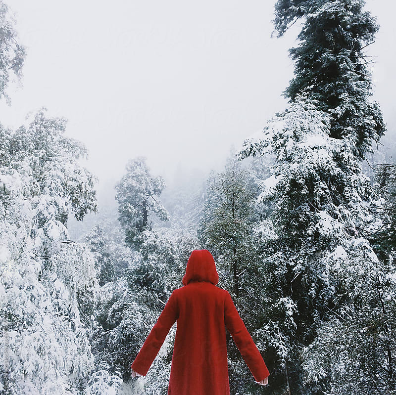 Girl in red coat in front of snow by Ben Sasso for Stocksy United