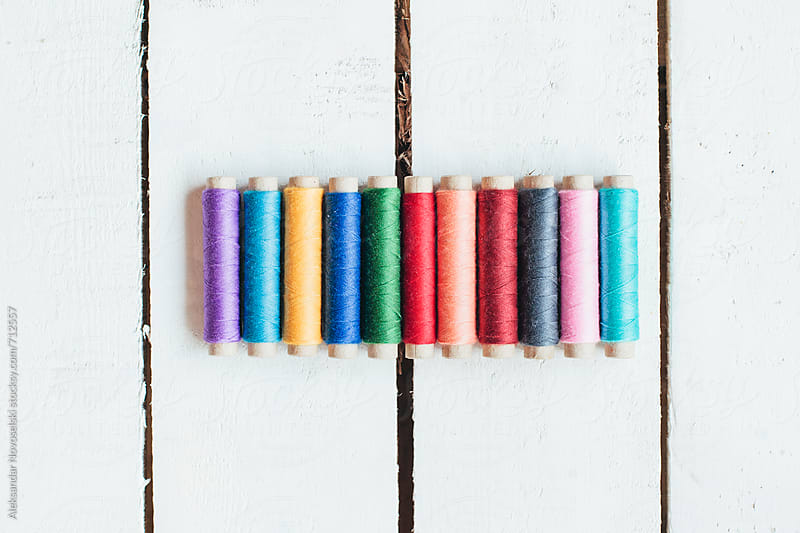 Arrangement of colorful threads against white wooden background by Aleksandar Novoselski for Stocksy United