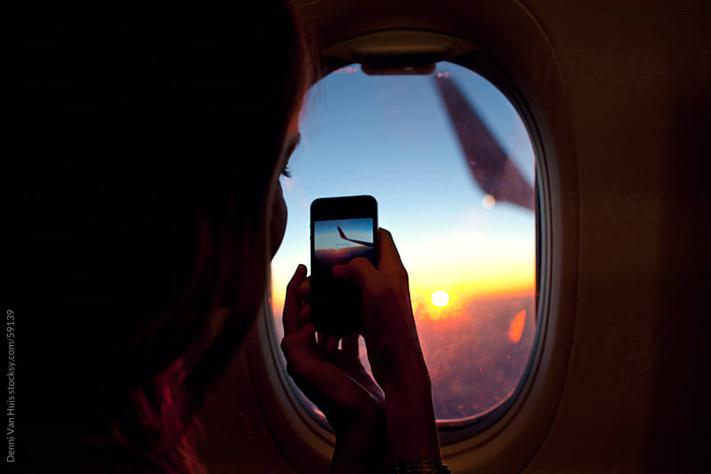 Young woman sitting in a window seat in an airplane and is using her phone by Denni Van Huis for Stocksy United