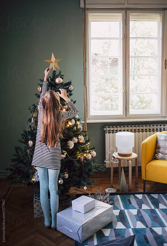 Caucasian Girl Decorating the Christmas Tree by Lumina for Stocksy United