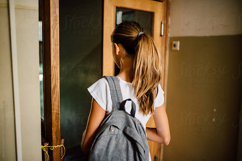 Girl with ponytail and backpack walking to the school by Boris Jovanovic for Stocksy United