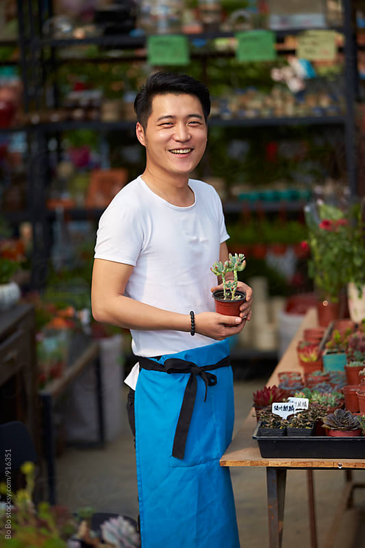 young male florist working in the shop by cuiyan Liu for Stocksy United