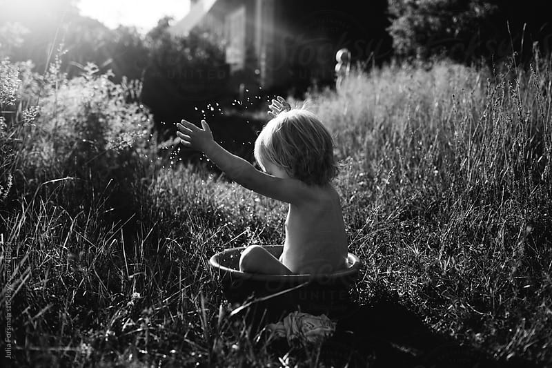 Little child washing in a tub outside in a meadow. by Julia Forsman for Stocksy United