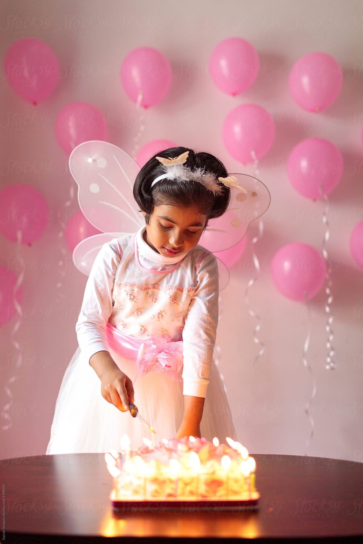 Little Girl Cutting Her Birthday Cake By Saptak Ganguly For Stocksy United