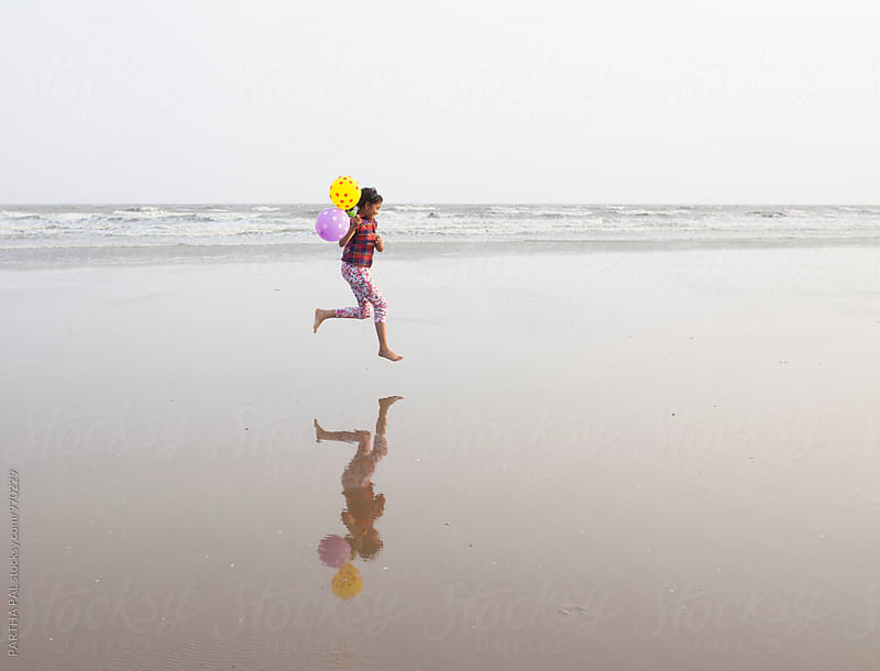 A girl running in beach holding balloon in hand by PARTHA PAL for Stocksy United