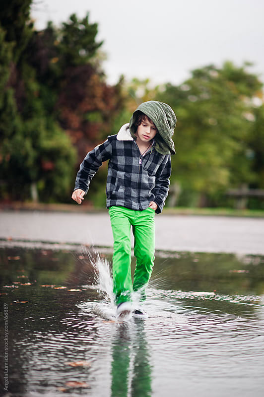 Boy splashing water in a large puddle by Angela Lumsden for Stocksy United