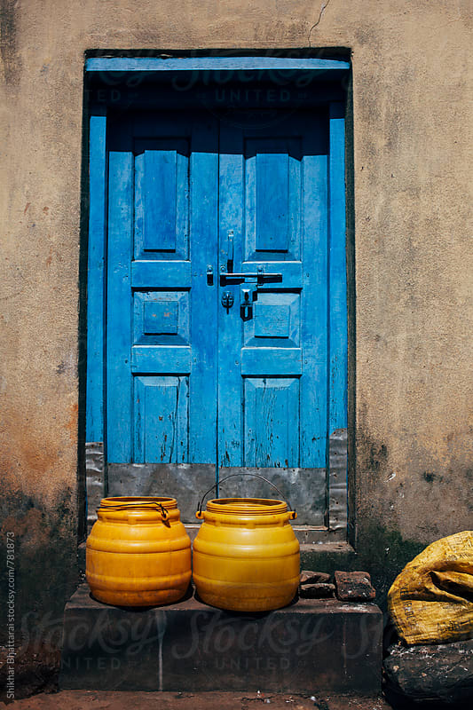 yellow buckets against a blue door. by Shikhar Bhattarai for Stocksy United