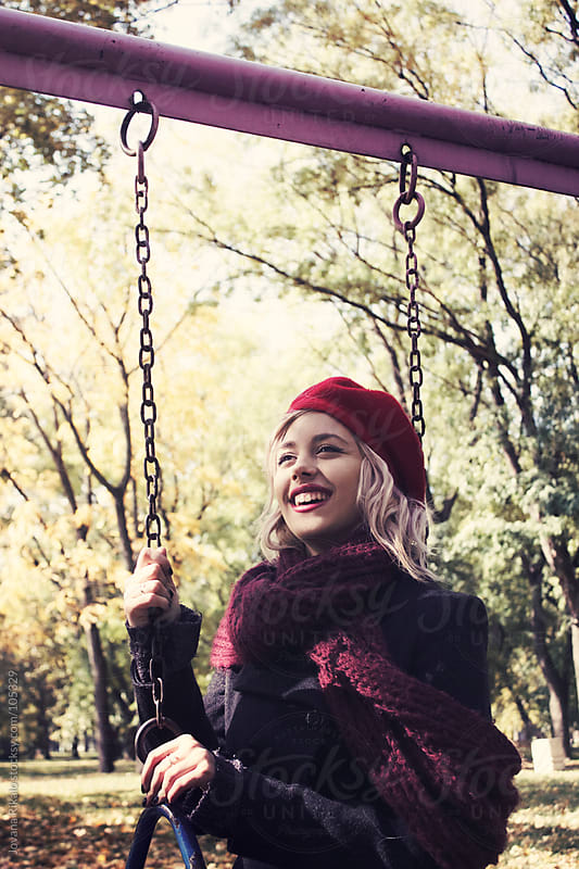 Beautiful young girl sitting on swing and smiling by Jovana Rikalo for Stocksy United