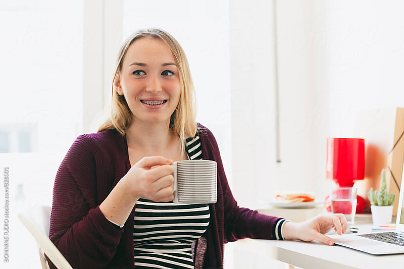 Portrait of a blonde woman drinking a cup of coffee at home office. by BONNINSTUDIO for Stocksy United