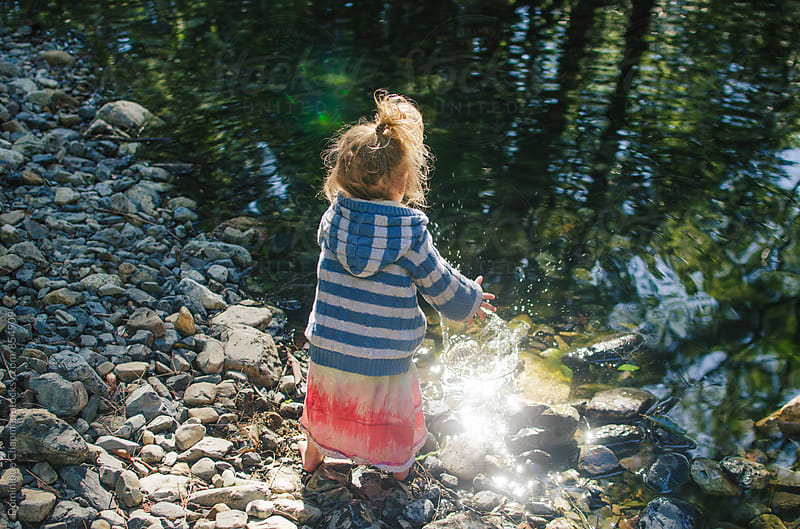 Little girl throwing rocks into river by Dominique Chapman for Stocksy United