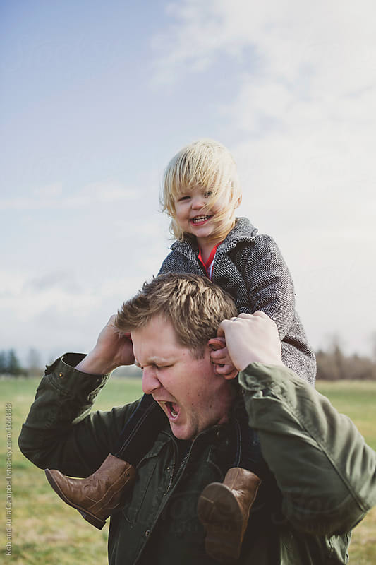 Funny toddler girl pinches dad's ears - pain for daddy by Rob and Julia Campbell for Stocksy United