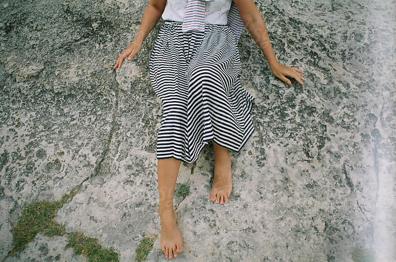 A film photo of young woman seating on the rock in the mountain of Cremea by Anna Malgina for Stocksy United