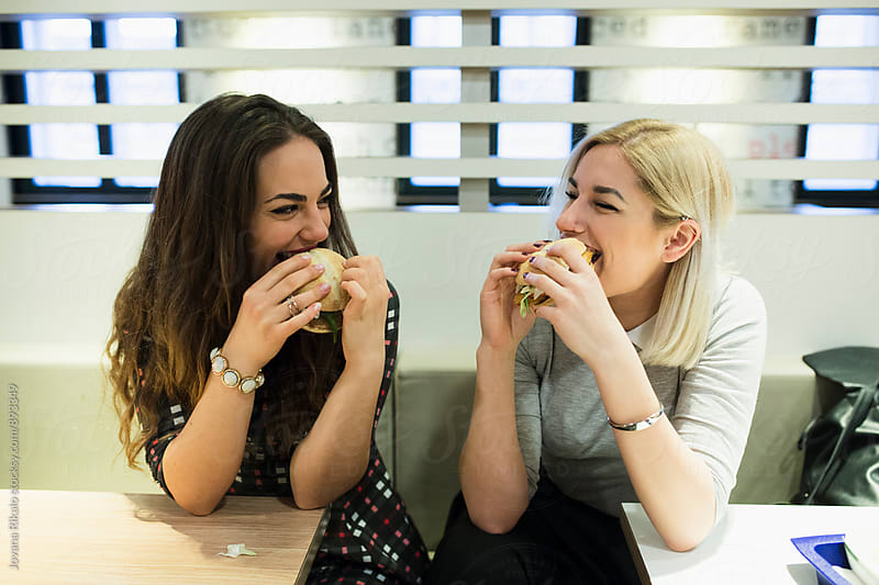 Two female friends eating burgers by Jovana Rikalo for Stocksy United
