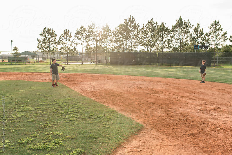 Two Boys Play Catch On A Baseball Diamond by Alison Winterroth for Stocksy United