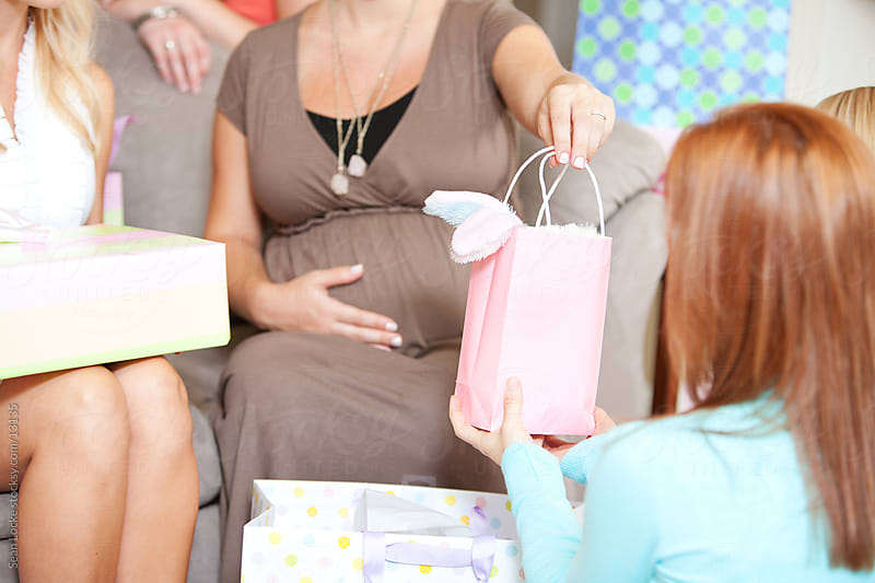 Baby Shower: Friend Hands Over Gift Bag by Sean Locke for Stocksy United