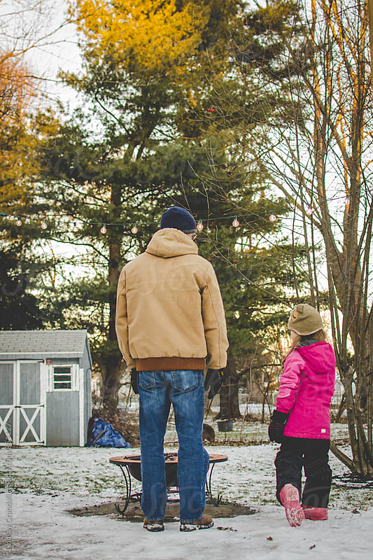 Father and daughter standing by fire pit in the winter by Lindsay Crandall for Stocksy United