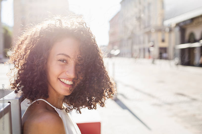 Portrait of beautiful curly woman  smiling by michela ravasio for Stocksy United