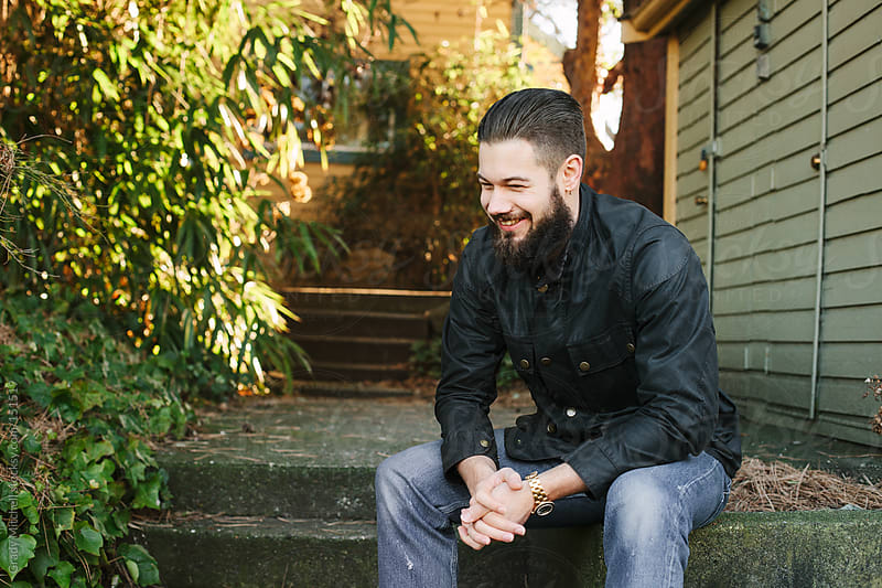 Laughing, Bearded Young Man On Steps by Grady Mitchell for Stocksy United