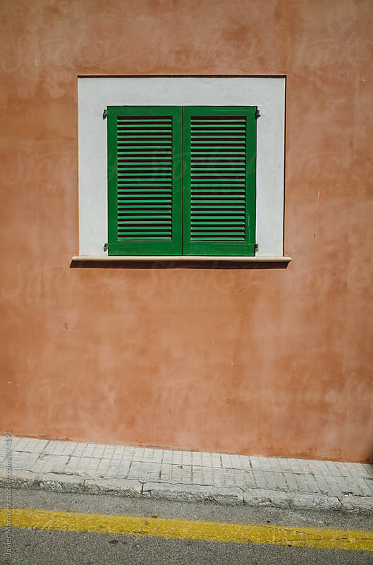 Green window in a red wall by Javier Márquez for Stocksy United