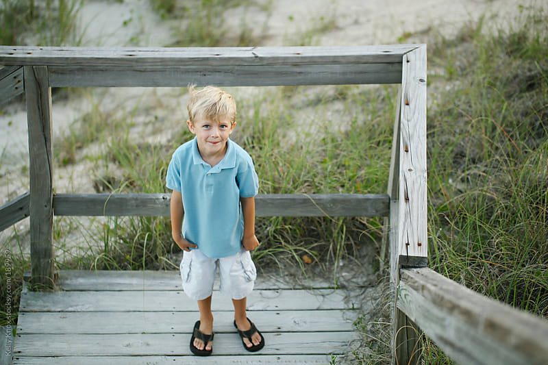 smiling boy at the bottom of a beach boardwalk by Kelly Knox for Stocksy United