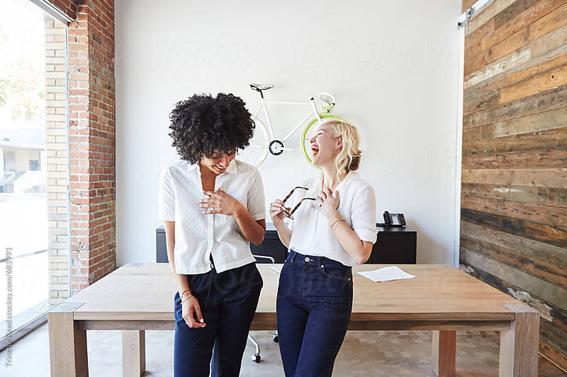 Portrait of millennial businesswomen laughing in office by Trinette Reed for Stocksy United