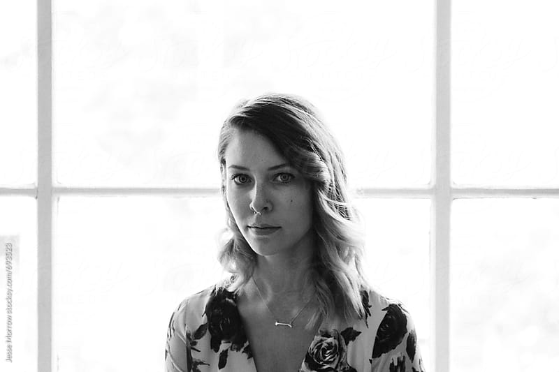 portrait of young woman in front of bright window in black and white by Jesse Morrow for Stocksy United