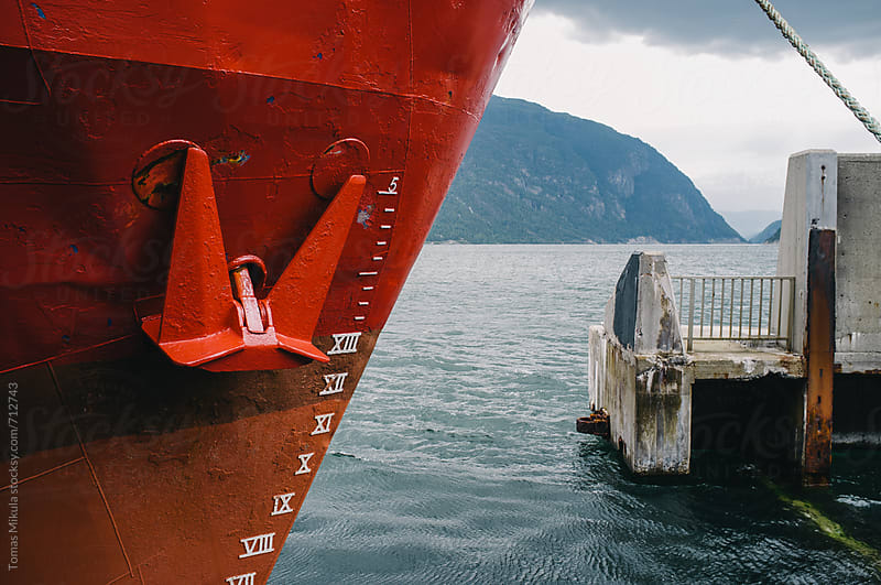 Red cargo ship in the port by Tomas Mikula for Stocksy United