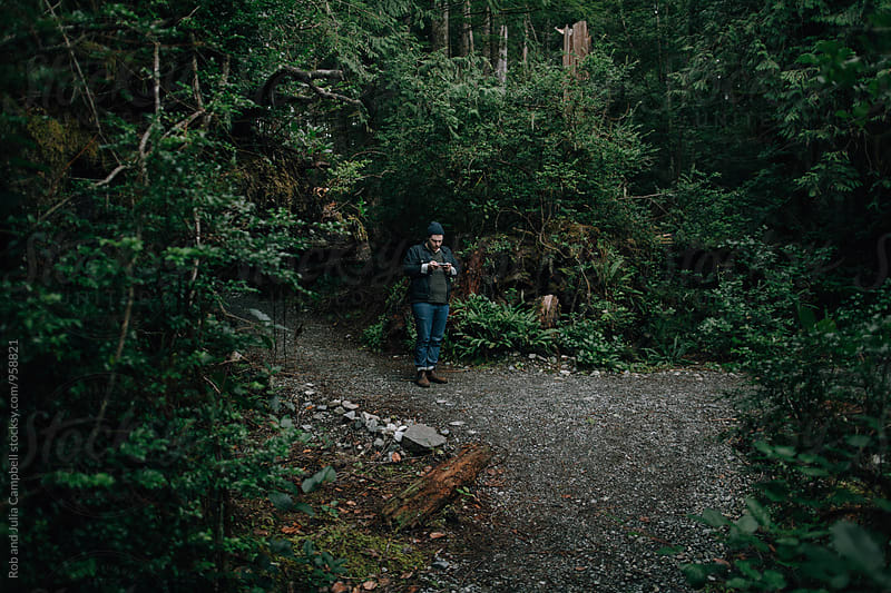 Mid 30's man on mobile phone outside in forest by Rob and Julia Campbell for Stocksy United