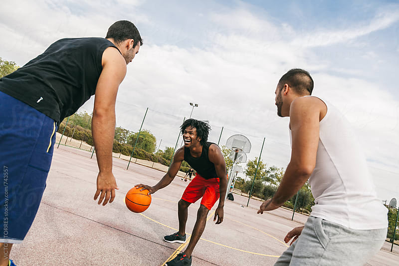 Three Friends Playing in a Street Basketball Court by Victor Torres for Stocksy United