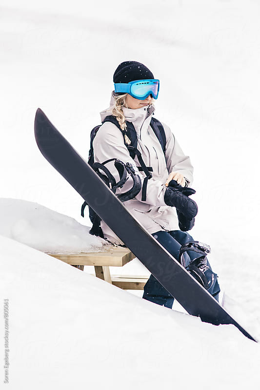 Female snowboarder sitting in the snow putting on gloves by Søren Egeberg Photography for Stocksy United