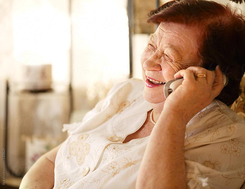 Senior woman talking on cellphone by Ilya for Stocksy United